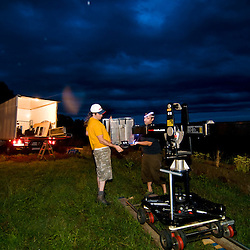 Two crew members set up the traveling while ominous clouds build in the background.