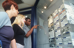 Multiracial group of young people looking at job vacancies displayed in window of recruitment agency,