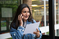 """© Licensed to London News Pictures. 15/08/2016. Sutton Coldfield, West Midlands,UK. Bishops Vesey's Grammar School pupils celebrating their A level results. Pictured, Sofia Kaur, 18, rings her parents to tell them the good news. Headmaster Dominic Robson said, """"The pupils had done amazingly well, achieving 80% A star and B grades especially given the change to the marking of the A level system this year. Photo credit: Dave Warren/LNP"""