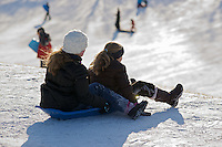 Two girls about to go down a hill on their toboggan in Whithrow Park, Toronto.