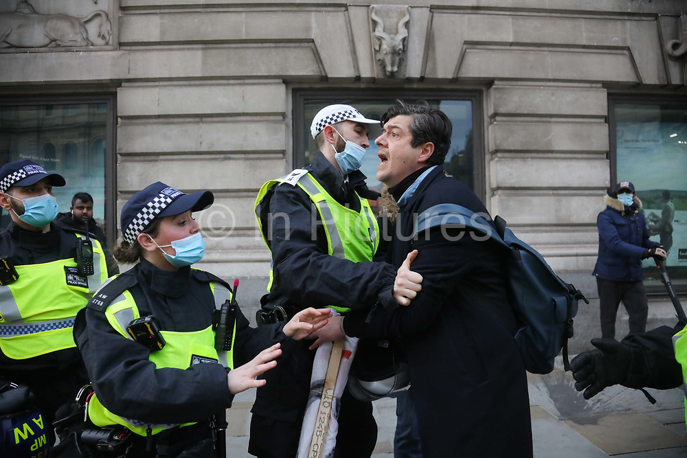Kill the Bill demonstration in Central London against the proposed Police, Crime, Sentencing and Courts Bill on the 3rd April 2021, London, United Kingdom. A man upset with fellow protesters is asked to leave the area by police. He was not arrested. After the protest ended in Parliament Square police cleared the streets, arresting several in the process. Thousands turned out in London and across the UK to show their objection to the Governments proposed bill. Many fear the bill is meant to suppress acts of protesting and demonstrations. The police will be given greater powers to prevent and stop actions of civil disobedience and peaceful protests and many see this as a suppression of their civil liberties. Sentencing for acts of peaceful protest is also likely to be much harsher and that may also act as a deterrent to protest.
