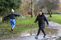 © Licensed to London News Pictures. 05/02/2021. London, UK. Women avoid walking through the puddle of water in Chestnuts Park, north London. Part of the footpath in the park is flooded following heavy overnight rain in London. According to the Met Office, snow is forecast for the weekend. Photo credit: Dinendra Haria/LNP