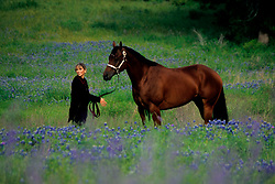 woman standing with a horse in a field of bluebonnets