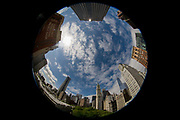180 degree distorted fish-eye lens cityscape on Broadway, Lower Manhattan, New York City. The extreme nature of this specialist lens bends straight lines and translates them into curves to show a skyline of the city of NYC, blue sky surrounded by tall skyscrapers in this modern metropolis. New York City, with a Census-estimated population of over 8.4 million in 2013, is the most populous city in the United States. Alone, it makes up over 40 percent of the population of New York State.