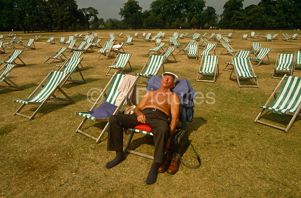 With dozens of deck chairs behind him, a sleeping middle-aged man lies bare-chested with a flat cap on his head and with his socks on as all Englishmen tend to do during a summer heat wave. He has chosen a spot in a near-empty Hyde Park in central London - an oasis of calm  amid a bustling city – where a seat in a striped deck chair can be rented for a few Pounds for the day and one can snooze topless without being bothered and one's stresses of daily life can be momentarily forgotten. With one hand resting on his leg, the other reaches down to hold on to his shoulder bag which is in the shade on the short grass.