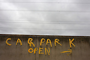 Letting coloured in yellow painted on a wall says Car Park Open, in Canning Town, Newham, East London..