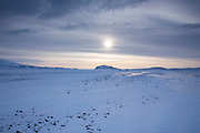 Wintry sun and clouds above snow-covered glacial landscape and lava fields in South Iceland