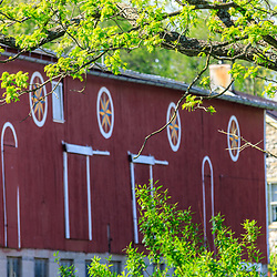 Hamburg, PA, USA- May 12, 2012: A red Pennsylvania Dutch barn with large round Hex signs in Berks County, PA.