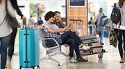 Couple assis sur un banc dans l'aéroport de la Tontouta en Nouvelle Calédonie. Photothèque Aircalin