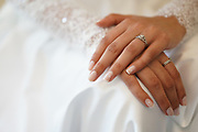 manicured hands of a bride with wedding ring