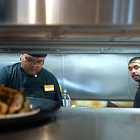 Cooks Terry Benally, left, and Omar Aguilar plate food to be served at the Denny's in Chinle Wednesday.