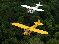 Two vintage Piper Cub airplanes fly in formation near Fishers, IN