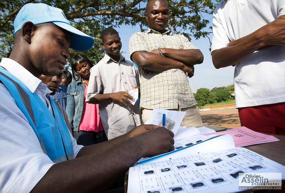 A worker from the Ghana Electoral Commission checks the identity of a voter during presidential and parliamentary elections in Accra, Ghana on Sunday December 7, 2008..