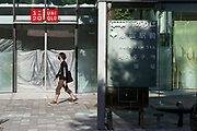 A young man wearing a face mask  COVID-19 walks past new, unopened stores in a redeveloping  Harajuku, Tokyo, Japan. Thursday May 7th 2020 The month-long state of emergency declared by the Japanese government in response to the COVID-19 pandemic was due to end on May 7th but was extended to May 31st despite Japan appearing to have avoided the high infection and mortality rates of some countries. Areas like Shibuya have many businesses shuttered and closed and the streets are a lot quieter than usual.
