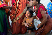 After bathing and religious rituals, a Hindu mother and her daughter are walking out of the holy Ganges River during the yearly Sonepur Mela, Asia's largest cattle market, in Bihar, India.