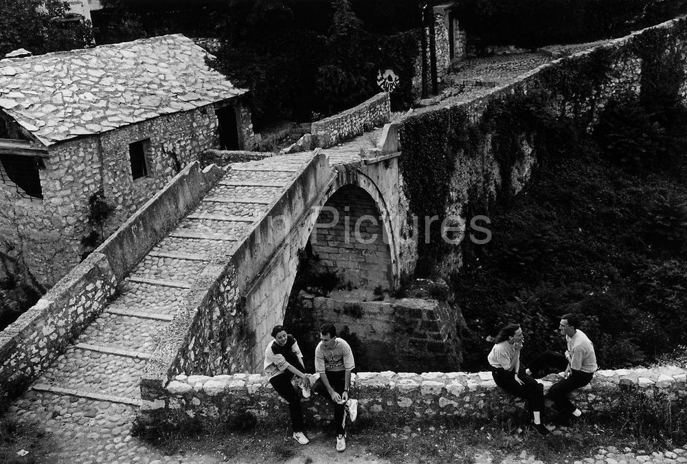 "People returning to some sense of normality amidst the ruins after the Dayton Peace Accords. It was destroyed by systemic bombardment from Croat guns during the Croat Muslim War, when the Croats endeavored to "" cleanse"" the town of non Croats. Mostar, Bosnia and Herzegovina."