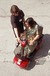 Trainer teaching woman with disability how to use motorised scooter,
