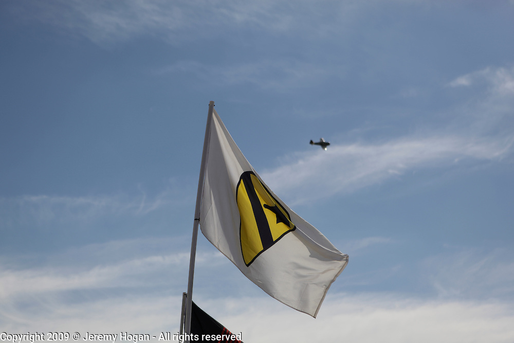 An airplane does a fly over with the First Cavalry flag in the foreground during the Vietnam Veterans gathering in Kokomo, Indiana for the 2009 reunion.