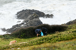 © Licensed to London News Pictures. 25/08/2020. City, UK. A family hide behind a bush to shelter from the strong winds in Langland Bay, Gower, as Storm Francis brings poor weather conditions across the UK with high winds and heavy rain causing disruption. Photo credit: Robert Melen/LNP