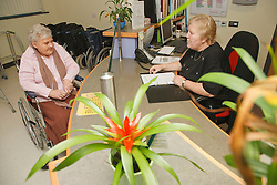 Receptionist with wheelchair user at reception for a resource for people with physical and sensory impairment.