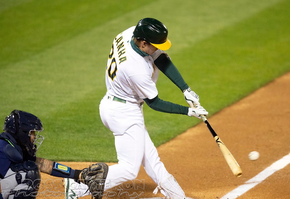 Sep 25, 2020; Oakland, California, USA; Oakland Athletics left fielder Mark Canha (20) connects for a double against the Seattle Mariners during the fourth inning of a Major League Baseball game at Oakland Coliseum. Mandatory Credit: D. Ross Cameron-USA TODAY Sports