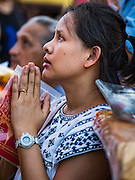 21 NOVEMBER 2015 - BANGKOK, THAILAND: A woman prays at the Wat Saket temple fair. Wat Saket is on a man-made hill in the historic section of Bangkok. The temple has golden spire that is 260 feet high which was the highest point in Bangkok for more than 100 years. The temple construction began in the 1800s in the reign of King Rama III and was completed in the reign of King Rama IV. The annual temple fair is held on the 12th lunar month, for nine days around the November full moon. During the fair a red cloth (reminiscent of a monk's robe) is placed around the Golden Mount while the temple grounds hosts Thai traditional theatre, food stalls and traditional shows.     PHOTO BY JACK KURTZ