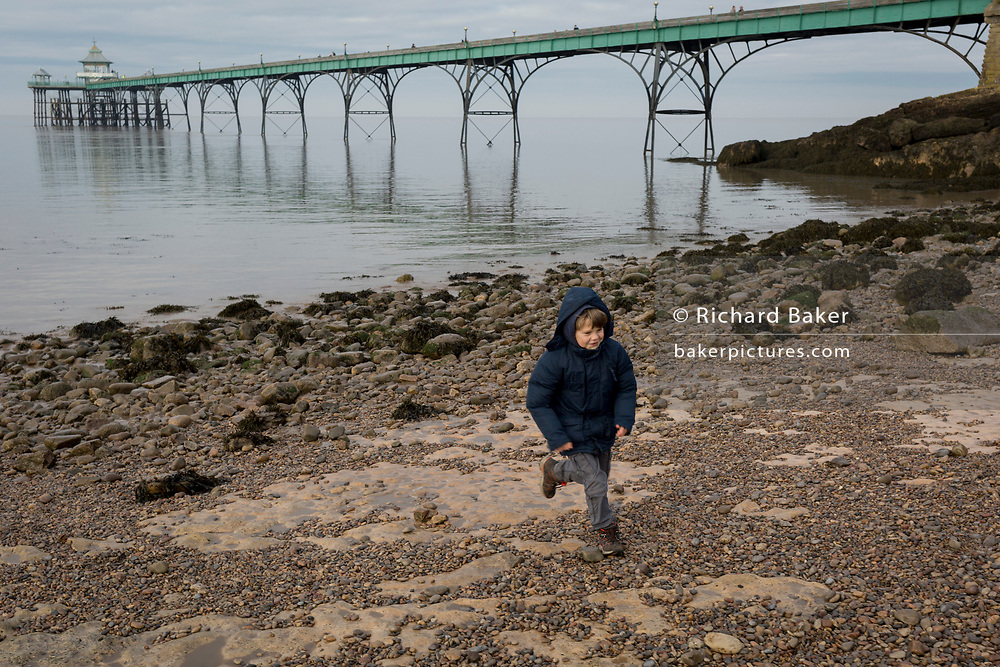 A 9 year-old boy runs on the beach at Clevedon Pier, on 27th December 2018, in Clevedon, North Somerset, UK.