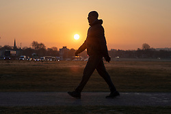 © Licensed to London News Pictures. 18/04/2021. London, UK. A man walks during sunrise on Blackheath Common in South East London. Temperatures are expected to rise with highs of 17 degrees forecasted for parts of London and South East England today . Photo credit: George Cracknell Wright/LNP
