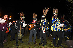 © London News Pictures. 05/01/2018. Hartley Wintney, UK. Hook Eagle Morris Men sings songs and play music in an orchard, following torch-lit parade as part of a Wassailing tradition in the town of Hartley Wintney in Hampshire, England. Wassail is a traditional Pagan winter celebration in cider-producing regions of England, reciting incantations and singing to the trees to promote a good harvest for the coming year. Photo credit: Ian Longthorne/LNP