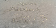 "The phrase ""New Zealand 2013"" is scratched into the sand on the beach at Mason Bay, Stewart Island (Rakiura), New Zealand"