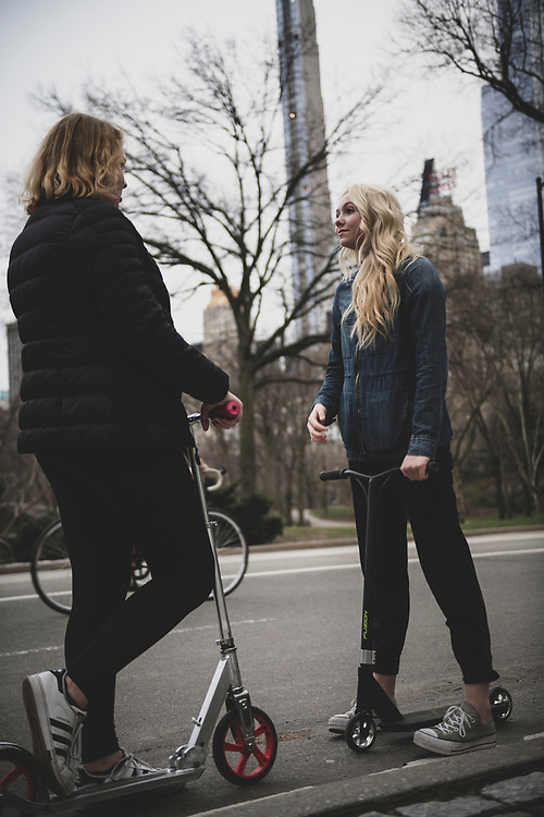 New York City, USA - March 18, 2020: High school seniors Amelia Ward and Rylee Rogers spend time together in Central Park. With schools closed due to the pandemic, plans for traditional senior-year milestones, like prom, were suspended.
