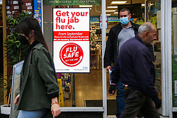 © Licensed to London News Pictures. 13/10/2020. London, UK. Members of public wearing a face coverings walk past a 'Flu Jab' advert in a pharmacist window in north London. According to research, a flu jab  could offer some vital protection against Covid-19. GPs and pharmacies are to vaccinate almost 30 million people in England against flu in the next two months to help prevent the health service collapsing under the joint burden of a flu outbreak and Covid-19. Photo credit: Dinendra Haria/LNP