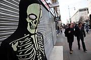 People walking past a skull skeleton suit on Oxford Street in London, United Kingdom.