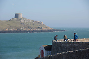 Standing at Coliemore Harbour, cyclists overlook Dalkey Island on 08th April 2017 in County Dublin, Republic of Ireland. Dalkey is one of the most affluent suburbs of Dublin, and a seaside resort just south of Dublin City. It was founded as a Viking settlement and became an active port during the Middle Ages.