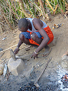 Forging heated iron nugget into shape with a hammer . Gidonwoduk tribe, the former Datoga blacksmith tribe. Today they are a separate tribe. They do not marry with Datoga since they discovered the secrets of blacksmithing. Photographed in Africa, Tanzania, Lake Eyasi
