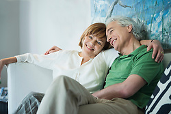 Couple relaxing on couch, smiling