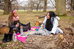 © Licensed to London News Pictures. 08/03/2021. London, UK. Friends Nati Siu 38 (left) and Sandra Chavez 42 meet for the first time since October 2020 as they enjoy a picnic in Richmond Park, South West London this afternoon. From today, two friends are now allowed to socialise out side of their household for a coffee or picnic for the first time in months. England begins Stage1 of the easing of lockdown today, with children returning to school, care homes allowing a visitor and friends being allowed to socialise out side of their bubble. However, pubs, shops and restaurants still remain closed. Photo credit: Alex Lentati/LNP
