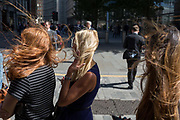 Young women endure strong wind blowing their hair everywhere on the street corner of Fenchurch Street in the City of London, aka The Square Mile the capitals financial district, on 3rd September 2019, in London, England.