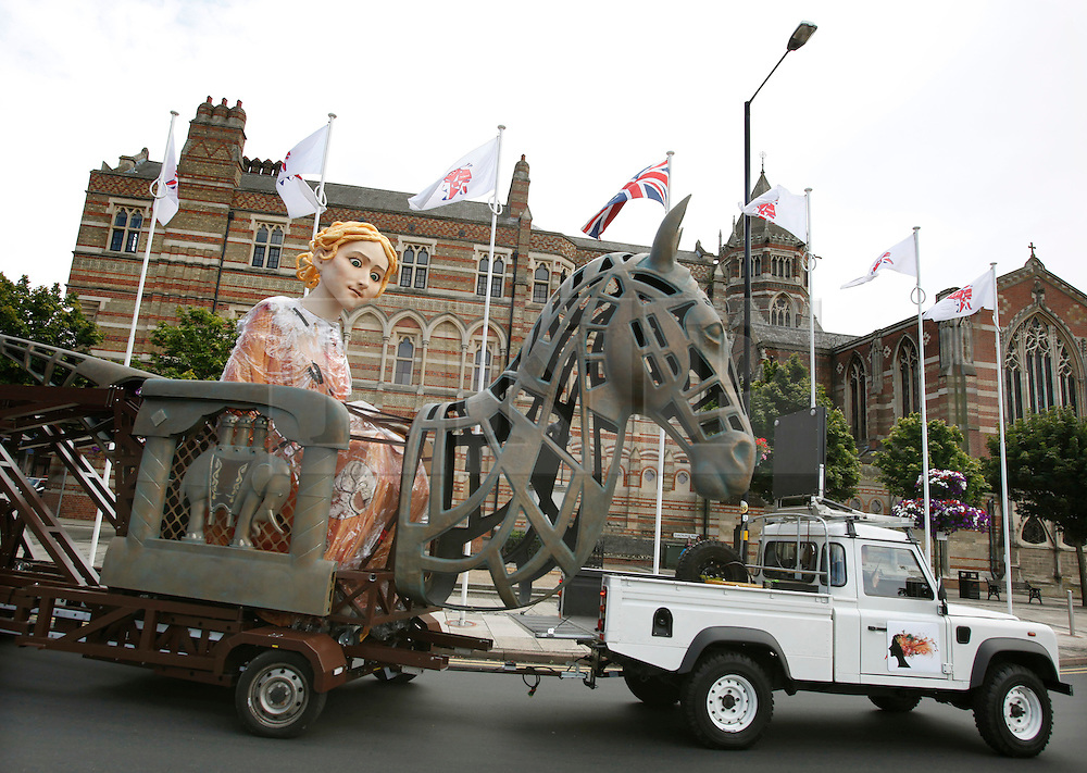 © Licensed to London News Pictures.30/07/2012. Rugby, UK. A 6m-high puppet of Lady Godiva arrived in Rugby today on the first stop of its journey from Coventry to London to celebrate the Olympics. The puppet, transported using a bike called the Cyclopedia, and powered by 100 cyclists will go to Northampton, Milton Keynes, Luton, Hatfield and Waltham Abbey before arriving at Waltham Forest on 5 August. Pictured, the puppet arrives in Rugby, passing Rugby School..Photo credit : Dave Warren/LNP