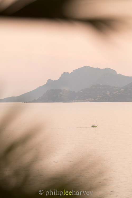 Sail boat on sea in misty morning with mountain on background, Cannes, France.