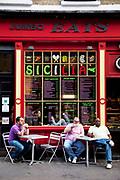 Men enjoying a coffee outside the Jumbo Eats Sicilia restaurant in Soho, London.
