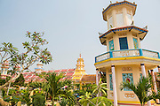 "29 MARCH 2012 - TAY NINH, VIETNAM:    A tower on the campus of the Cao Dai Holy See in Tay Ninh, Vietnam. Cao Dai (also Caodaiism) is a syncretistic, monotheistic religion, officially established in the city of Tây Ninh, southern Vietnam in 1926. Cao means ""high"" and ""Dai"" means ""dais"" (as in a platform or altar raised above the surrounding level to give prominence to the person on it). Estimates of Cao Dai adherents in Vietnam vary, but most sources give two to three million, but there may be up to six million. An additional 30,000 Vietnamese exiles, in the United States, Europe, and Australia are Cao Dai followers. During the Vietnam's wars from 1945-1975, members of Cao Dai were active in political and military struggles, both against French colonial forces and Prime Minister Ngo Dinh Diem of South Vietnam. Their opposition to the communist forces until 1975 was a factor in their repression after the fall of Saigon in 1975, when the incoming communist government proscribed the practice of Cao Dai. In 1997, the Cao Dai was granted legal recognition. Cao Dai's pantheon of saints includes such diverse figures as the Buddha, Confucius, Jesus Christ, Muhammad, Pericles, Julius Caesar, Joan of Arc, Victor Hugo, and the Chinese revolutionary leader Sun Yat-sen. These are honored at Cao Dai temples, along with ancestors.    PHOTO BY JACK KURTZ"