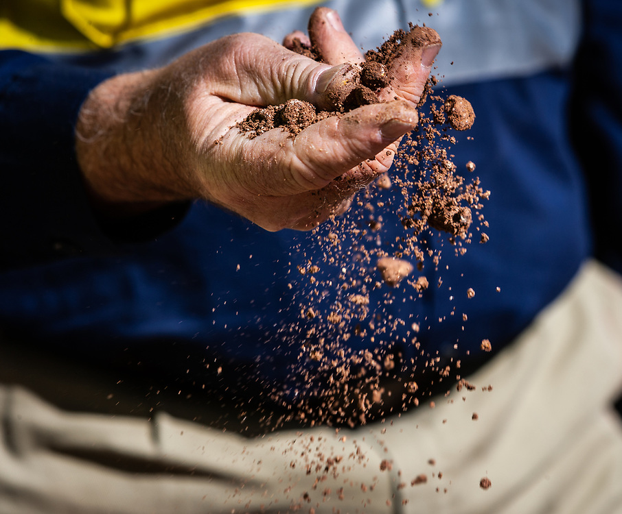Pilbara dirt is crushed through a workers hands in the Pilbara region of Western Australia.