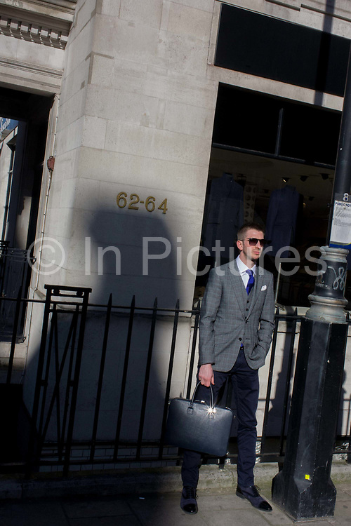 A stylish young man stands with a briefcase looking confident on a Mayfair street corner in central London.  Wearing dark sunglasses and with a hand in a pocket, the male stands next to a large shadow over his shoulder and with the numbers of an address in this part of central London. Mayfair is an exclusive area of West London, by the east edge of Hyde Park, in the City of Westminster. It is named after the annual fortnight-long May Fair that, from 1686 to 1764 but now the district is now mainly commercial, with many former homes converted into offices for major corporate headquarters, embassies, and also hedge funds and real estate businesses.
