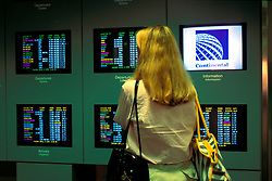 Woman Walking Past Monitors with Flight Arrival and Departure Information at George Bush International Airport