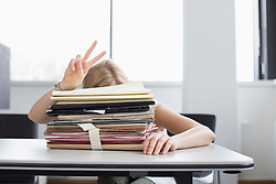 Businesswoman overwhelmed with stack of files