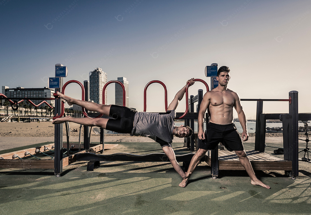 Two men practicing calisthenics in urban work out park in Barcelona Spain