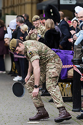 Windsor, UK. 25 February, 2020. A soldier from the 1st Battalion Welsh Guards drops his pancake as he competes on Shrove Tuesday in the Windsor and Eton Flippin' Pancake Challenge in aid of Alexander Devine Children's Hospice Service.