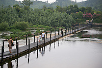 Family crossing a bridge to Sunny Park in  Anji, China 2009.