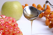 Pouring sweet sauce over fruit for dessert